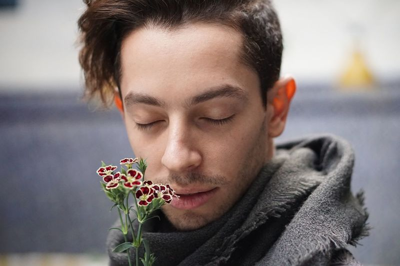 Close-Up Of Young Man With Eyes Closed Smelling Flowers
