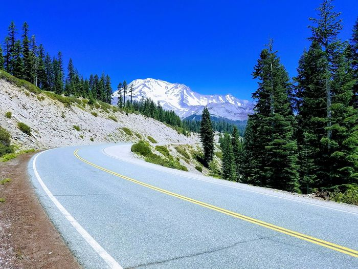 Empty road amidst trees leading towards mountains against clear sky