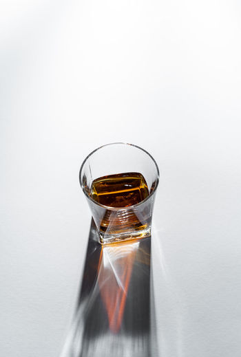 Close-up of wine glass on table against white background