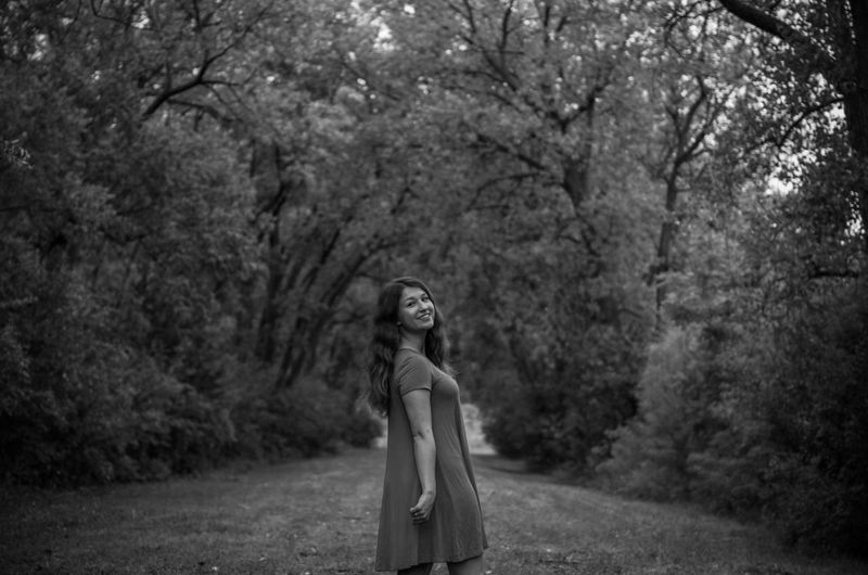 Portrait of beautiful girl standing amidst trees in forest