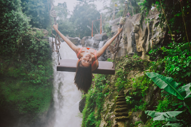 Young woman on swing against waterfall