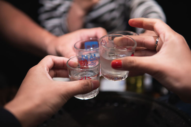 Close-up of hand holding glass of drink