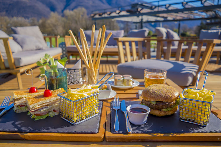 Hamburger and Club Sandwich Sunny Bread Business Color Day Drink Drink Glass Focus On Foreground Food Food And Drink French Fries Freshness Hamburger Healthy Eating Meal No People Plate Ready-to-eat Still Life Table Wellbeing