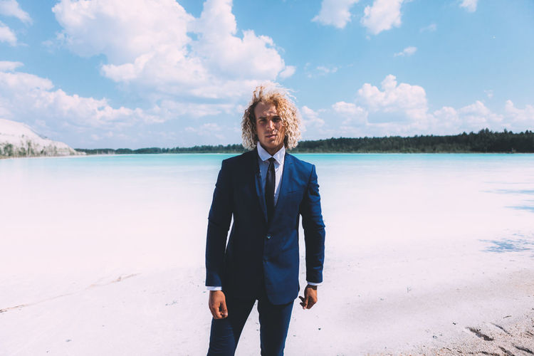 Blond curly man dressed in business suit is posing on the crystal clear lake. Trendy hairstyle, awesome shoot. Summer time. Beauty In Nature Cloud - Sky Day Front View Hairstyle Lake Leisure Activity Lifestyles Looking At Camera Nature One Person Portrait Real People Sky Smiling Standing Three Quarter Length Water