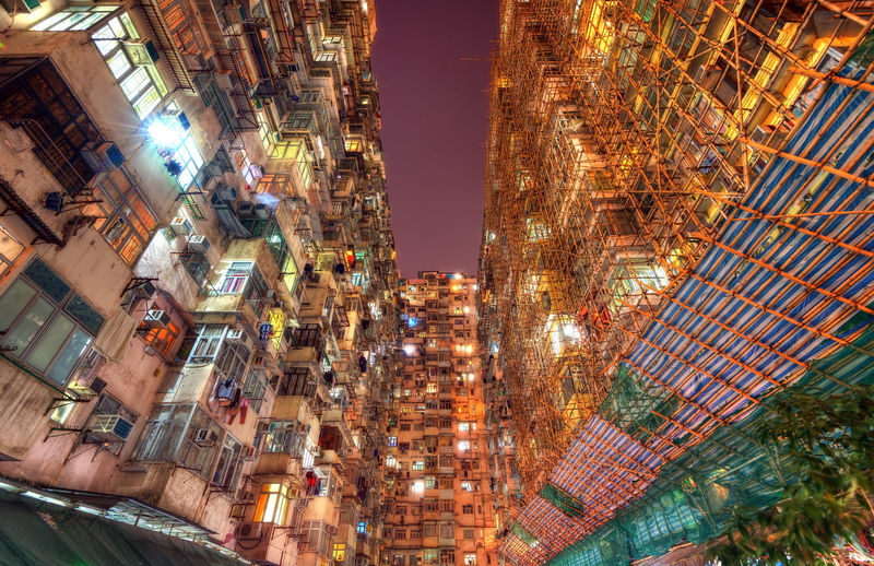Low angle view of illuminated buildings against sky in city