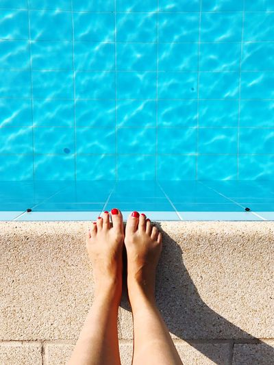Low section of woman standing at poolside
