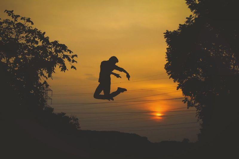 Silhouette man jumping on tree against orange sky