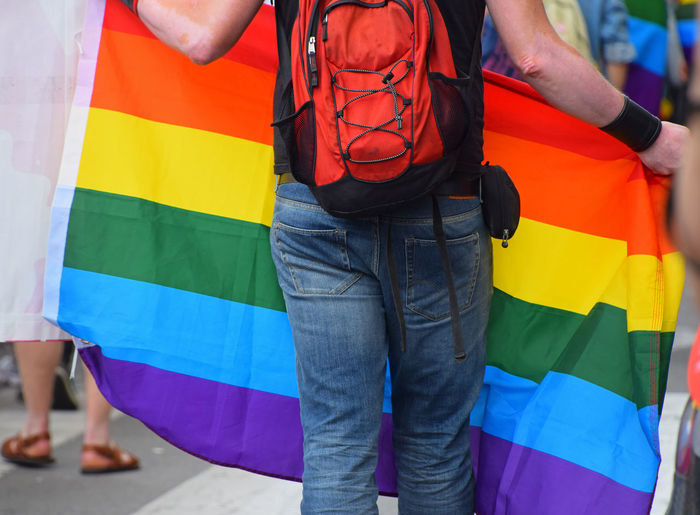 Midsection of man standing with rainbow flag