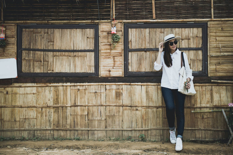 Woman in sunglasses standing against barn