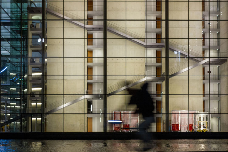 Blurred motion of person walking in modern building at night