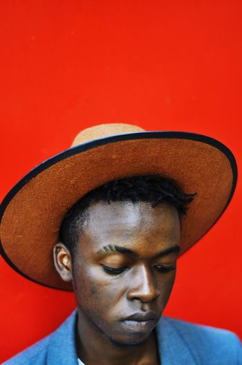 Close-Up Of Man Wearing Hat Against Red Wall