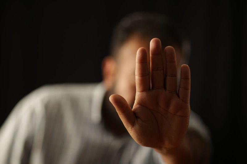 Man showing stop gesture against black background