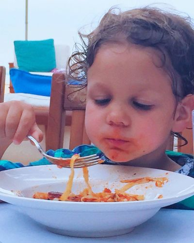 Young Boy Eating Pasta Holding Fork Food And Drink Childhood Headshot Elementary Age Unhealthy Eating Freshness Focus On Foreground Innocence Human Face White Bowl Spaghetti Cute Messy Face Curly Hair Puerta Viarta, Mexico