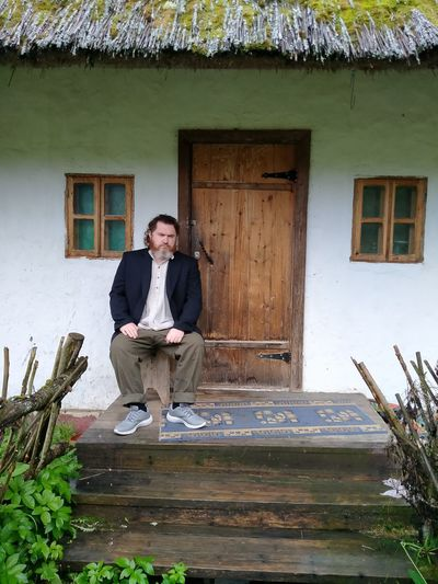 Full length portrait of young man standing outside house