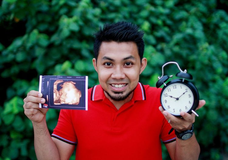 Portrait of young man holding alarm clock with ultrasound standing against plants