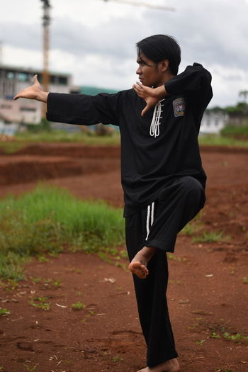 Young Man Practicing Karate On Field