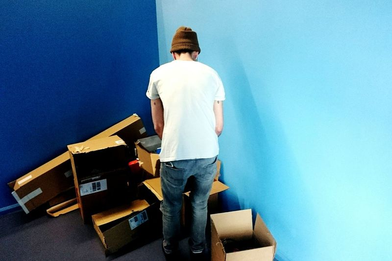 Rear View Of Man With Cardboard Boxes In Room