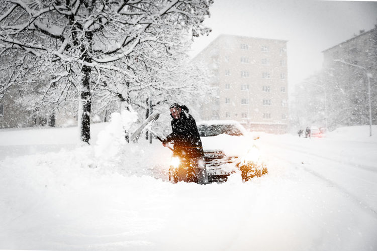 Man shoveling snow while standing by car in city