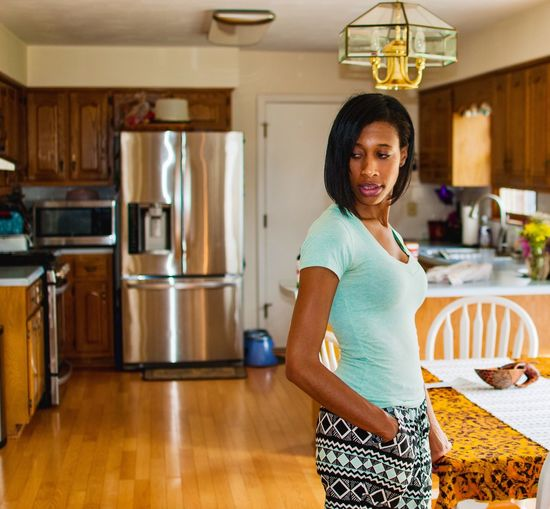 Side View Of Woman With Hand In Pocket Standing At Home