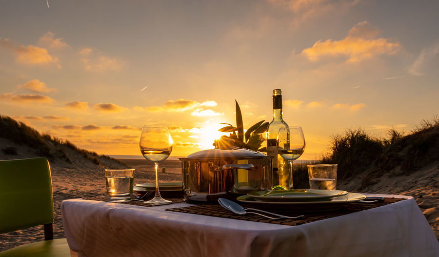 Drinks on table against sky during sunset