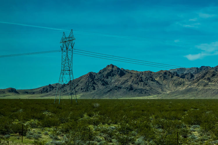 Low angle view of electricity pylon against mountain