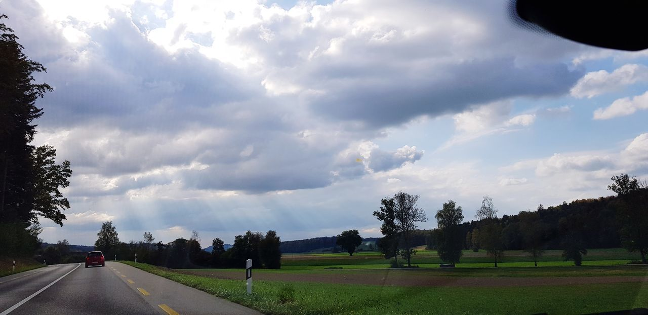 cloud - sky, sky, plant, transportation, tree, road, mode of transportation, nature, car, land vehicle, motor vehicle, grass, no people, day, beauty in nature, field, land, direction, environment, outdoors, long