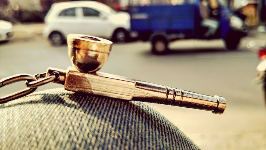 Close-Up Of Smoking Pipe Against Road