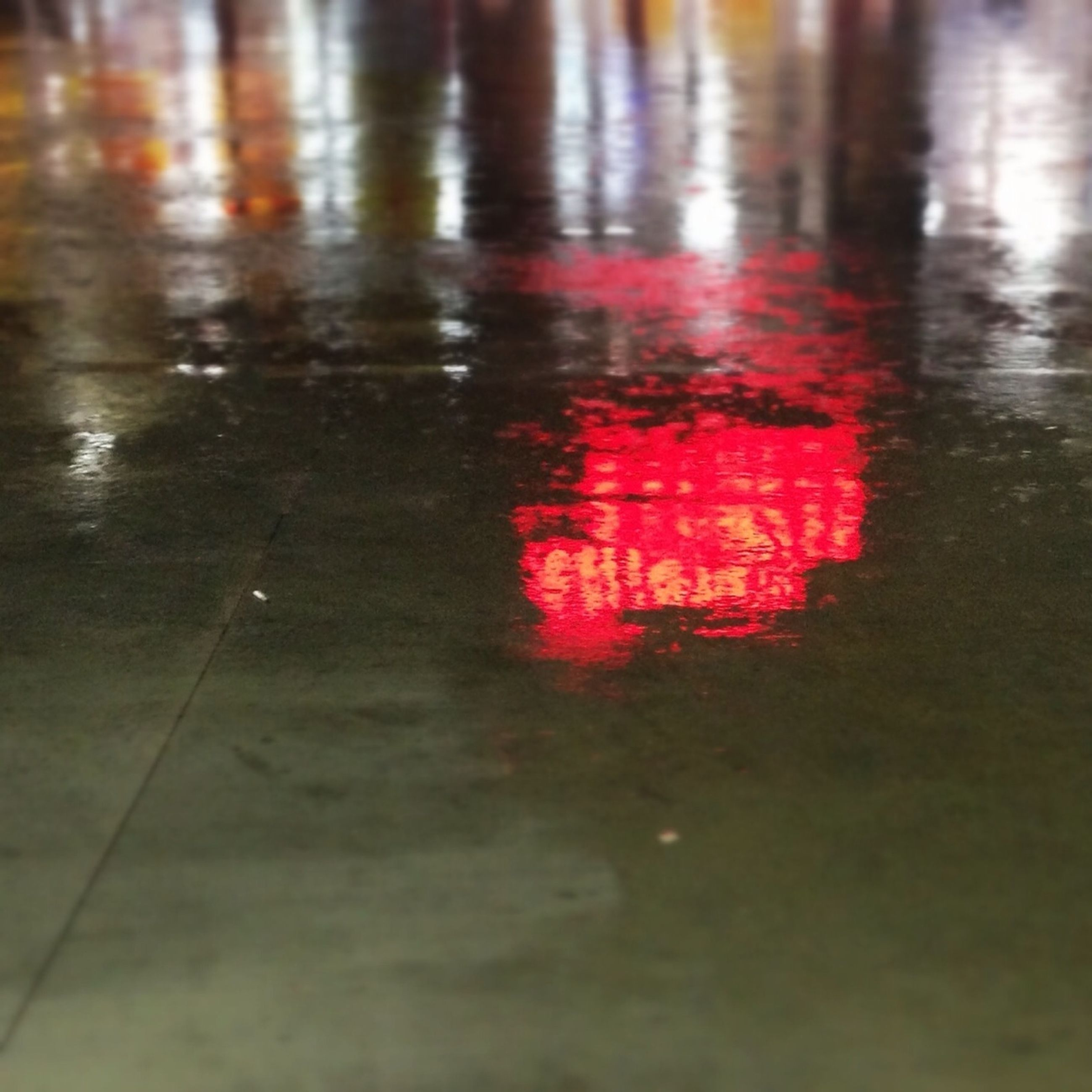 water, reflection, red, street, rain, high angle view, wet, road, text, transportation, puddle, communication, western script, safety, weather, outdoors, guidance, waterfront, no people, road sign