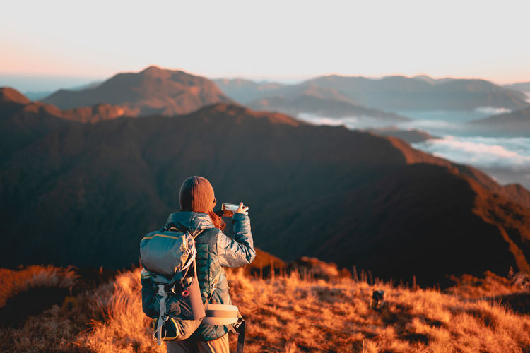 Adult female taking photo using her mobile phone at sunrise at mount pulag national park, benguet.