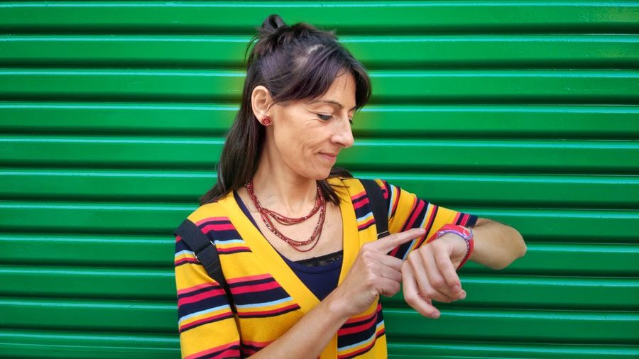 Woman wearing casual wear standing on the street and looking at her watch Woman Female Street Urban Casual Mature Females Watch Smartwatch Three Quarter Length Wall Jeans Standing Beautiful Trendy Casual Clothing Hipster Jersey Politics And Government Human Hand Multi Colored Portrait Headshot Colored Background Pride Women Green Background Pretty Posing Arm Band