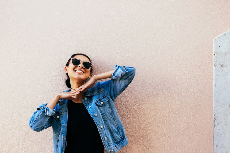 Happy Young Woman Wearing Sunglasses By Beige Wall