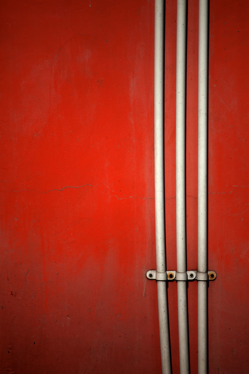 Electric pipes on a red wall