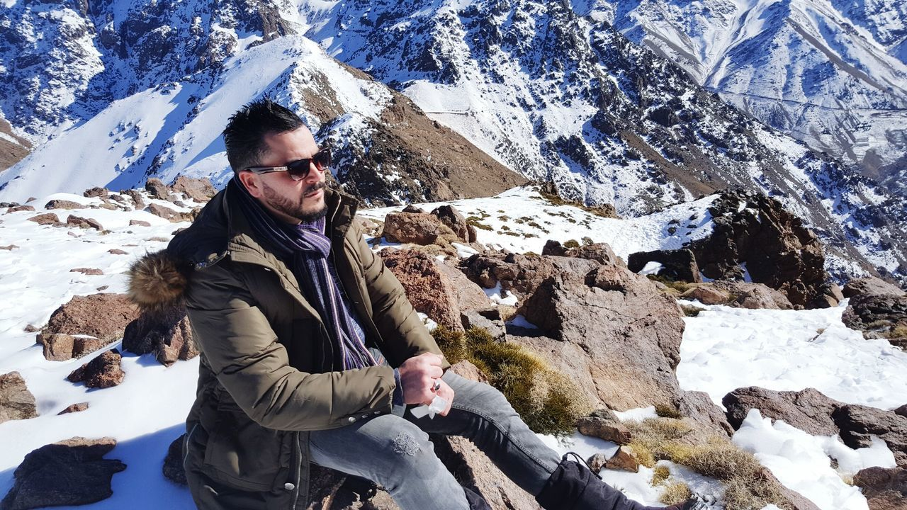 real people, leisure activity, lifestyles, one person, rock - object, young adult, casual clothing, young women, sunglasses, young men, front view, nature, outdoors, looking at camera, snow, winter, standing, day, cold temperature, portrait, beauty in nature, full length, warm clothing, sky