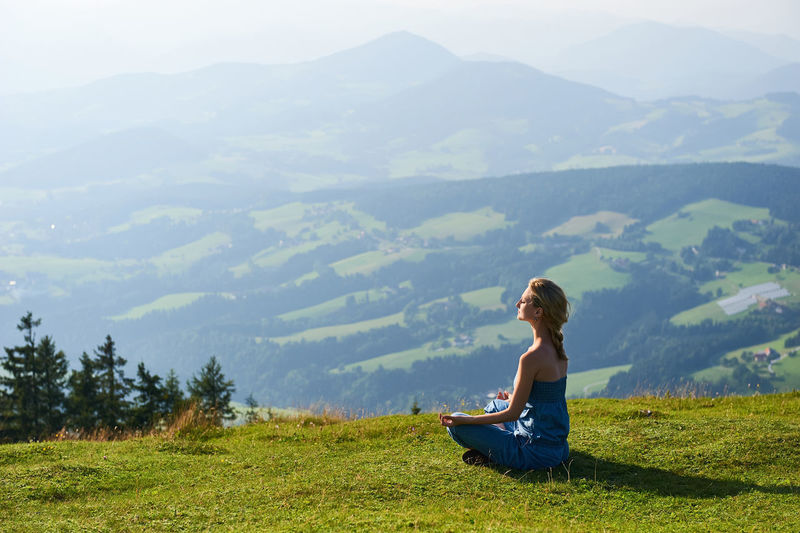 Young Woman Meditating On Grassy Field Against Mountains During Foggy Weather