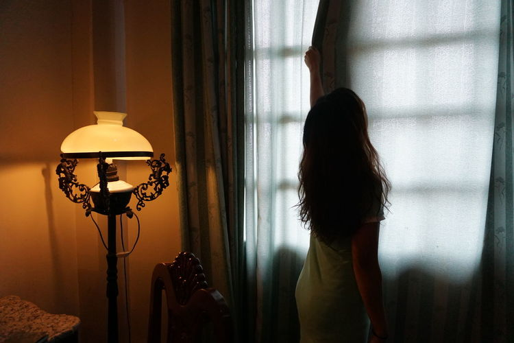 Rear view of woman closing curtain of window at home