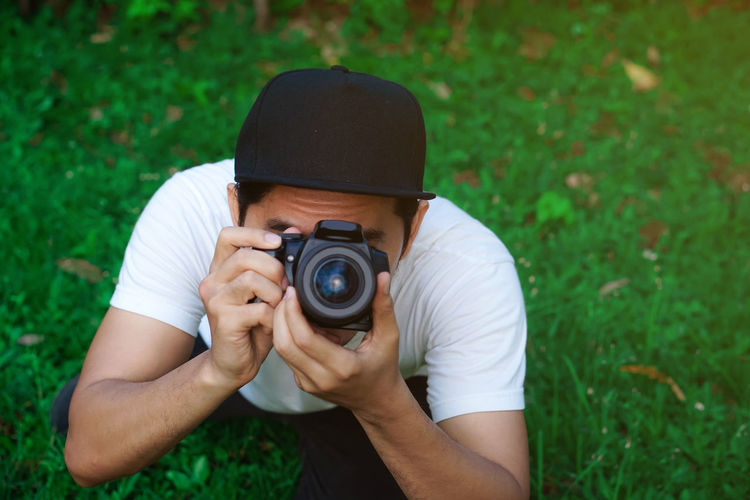 Midsection of man photographing camera