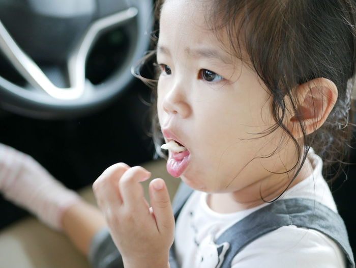 Close-up of girl eating food in car