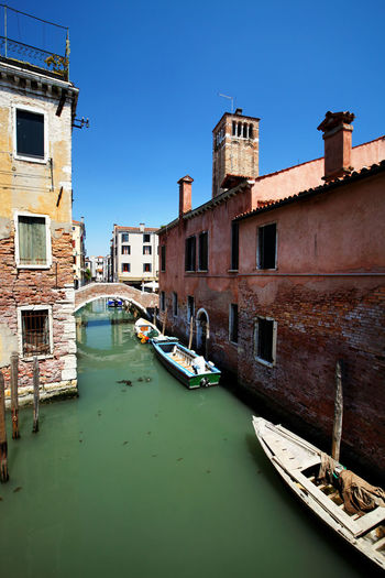 Boats moored on grand canal amidst buildings
