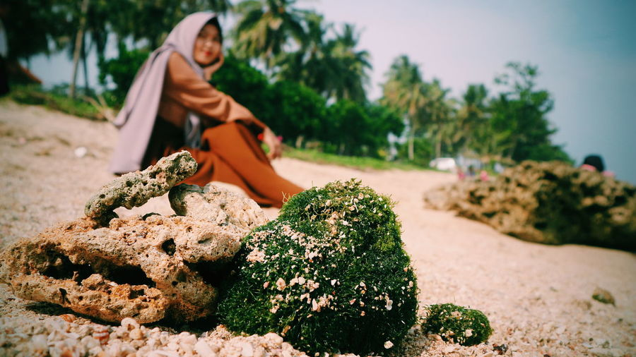 Young woman sitting by mossy rock at beach