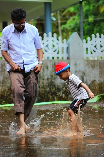 Father And Son Playing In Puddle