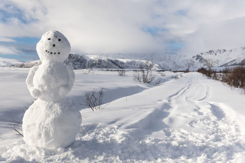 Snowman as tall as a man at empty snow covered road Beauty In Nature Cloud - Sky Cold Temperature Deep Snow Empty Road Full Length Landscape Lofoten And Vesteral Islands Nature No People Outdoors Polar Climate Remote Road Scenics Sky Snow Snowcapped Mountain Snowman Sunny Tall - High The Way Forward Tranquil Scene White Color Winter