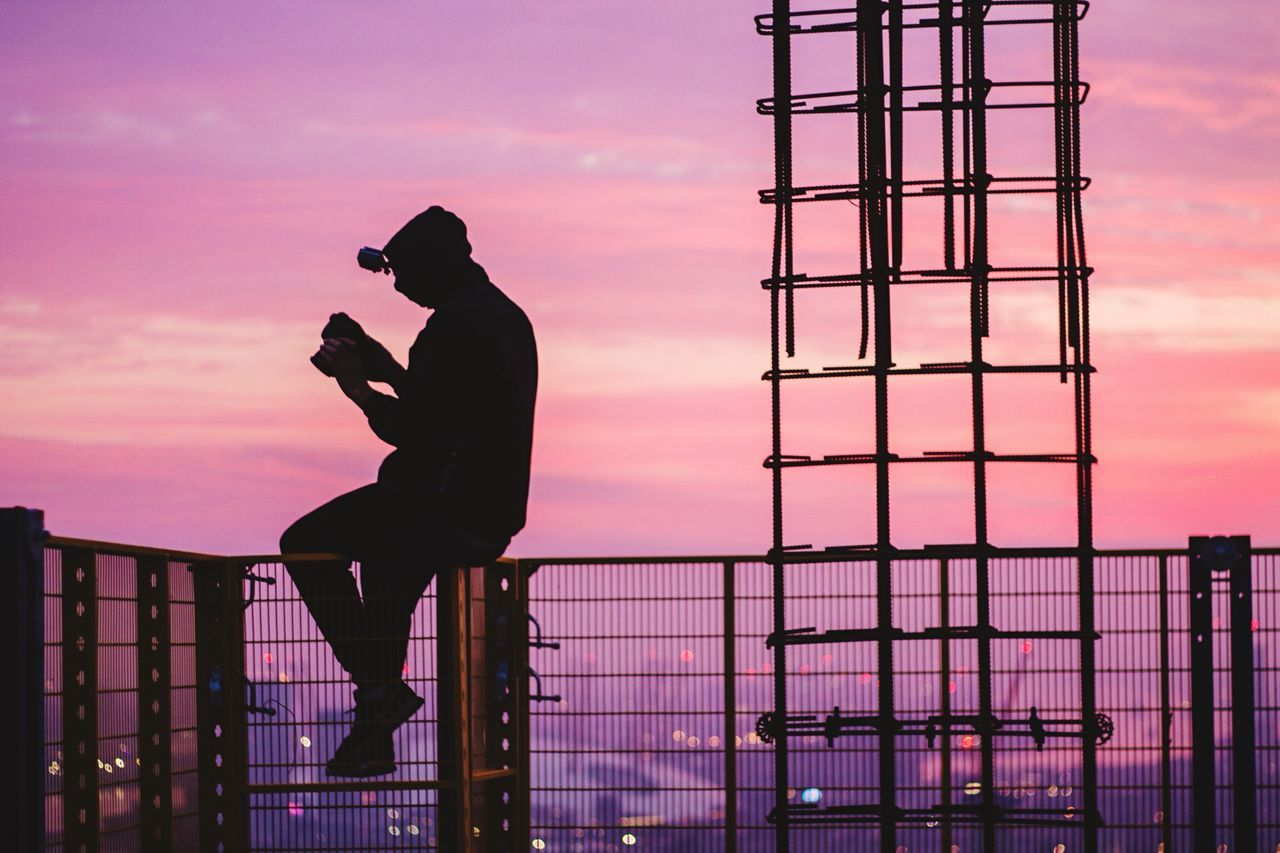 Side view of silhouette man holding camera while sitting on railing at sunset