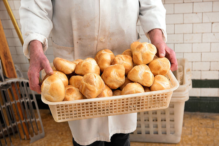 Midsection of man holding buns in basket