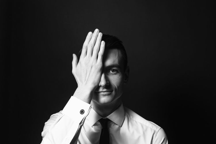 Portrait Of Businessman Covering Eyes With Hand Against Black Background