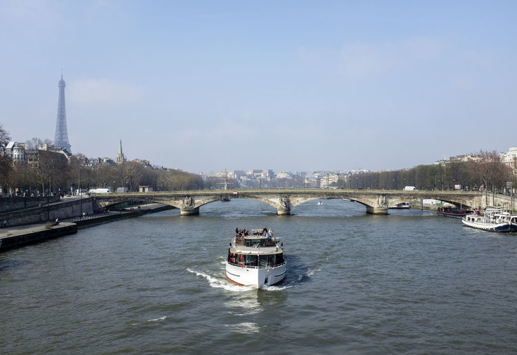 A sightseeing boat goes down the Seine Bridge - Man Made Structure City Cityscape Eiffel Tower Nautical Vessel River Transportation Travel Travel Destinations Urban Skyline Water