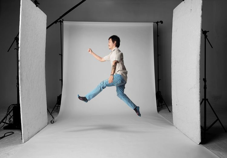 Young Man Jumping Against White Backdrop