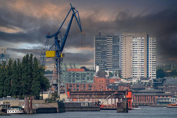 Cranes at harbor against buildings in city against sky