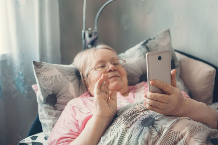 Senior woman using mobile phone while relaxing on bed at home