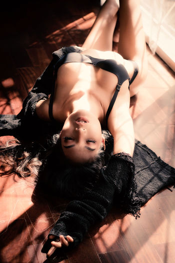 High Angle View Of Seductive Woman With Eyes Closed Lying On Floor At Home