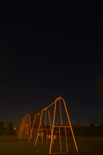 Low angle view of illuminated swings against sky at night
